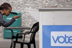 Eudora Carter carefully drops her ballot into a drop-off voting box Tuesday, Aug. 2, 2016, in Seattle. Washington's voters are weighing in on dozens of races across the state as they winnow their choices for offices ranging from Congress to the Legislature in the state's primary election. (AP Photo/Elaine Thompson)